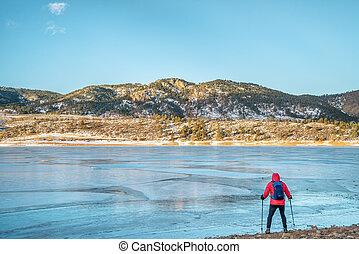 hiker at frozen mountain lake