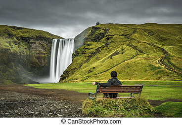 Hiker at the Skogafoss waterfall in southern Iceland