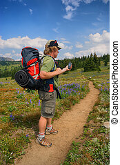 Hiker checks GPS - A hiker checks his handheld GPS along an...