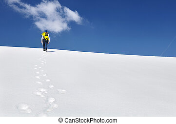hiker climbing mountain in the snow