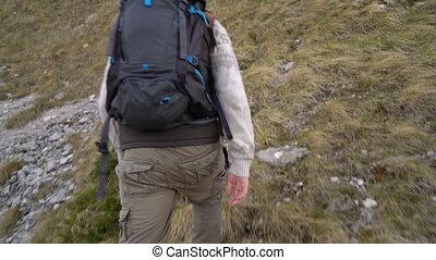 Hiker climbing the mountain slopes - Bearded hiker climbing...