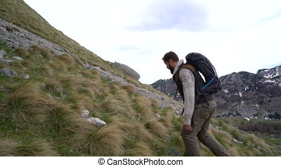 Hiker climbing the mountain slopes