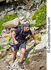 Hiker climbing the mountain - Caucasian hiker with backpack...