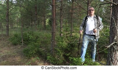 Hiker comes through overgrown forest