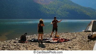 Hiker couple preparing tent near riverside on a sunny day 4k