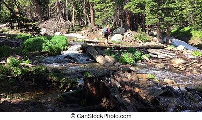Hiker Crosses a stream near Mitchell Lake Colorado - Hiker...
