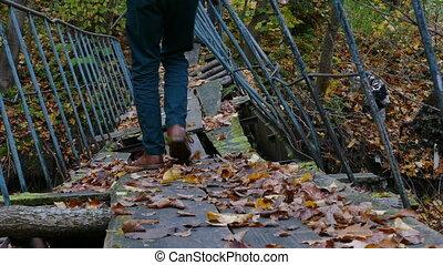 Hiker crossing old abandoned bridge - Hiker carefully...