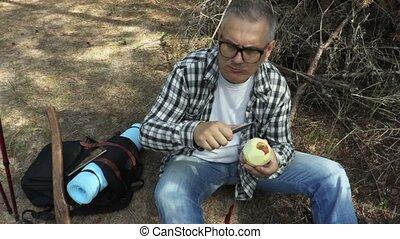 Hiker eats peeled apple