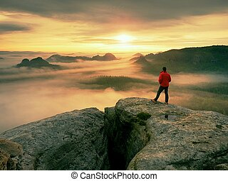 Hiker enjoy amazing view over heavy clouds. Rocky peak above valley.