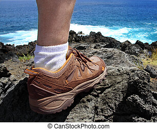 Hiker foot - A foot of a hiker standing on a lava coast of...