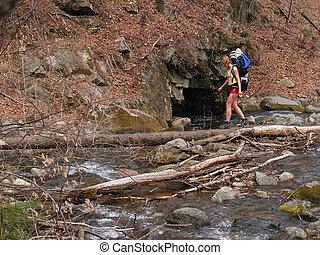 hiker girl crossing the river