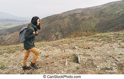 Hiker girl goes up in the mountain
