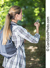 hiker girl searching direction with a compass in the forest