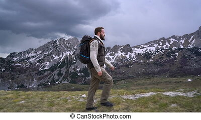 Hiker going along grassy slope