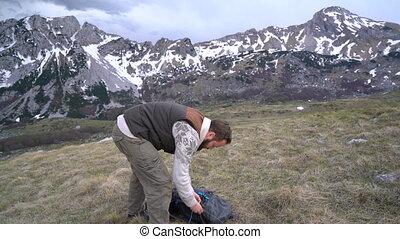 Hiker going along grassy slope