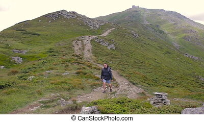 Hiker hiking in beautiful landscape. Man trekking walking with backpacks in mountains