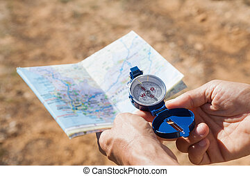 Hiker holding his compass and map i