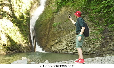 Hiker holds smartphone trying to find connection in deep forest with waterfalls.