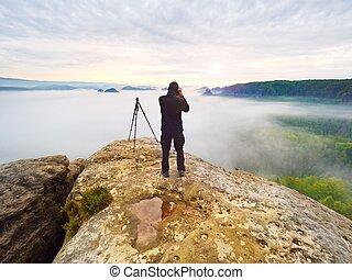 Hiker in black on the rocky peak. Wonderful daybreak in mountains, heavy orange mist in deep valley.