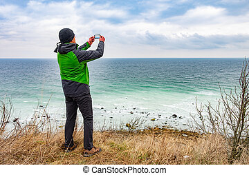 Hiker in green rain jacket  takes photos by phone - Hiker in...