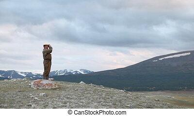 Hiker in mountain look into binocul