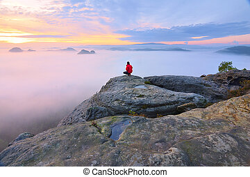Hiker in squatting position on peak of rock and watching...