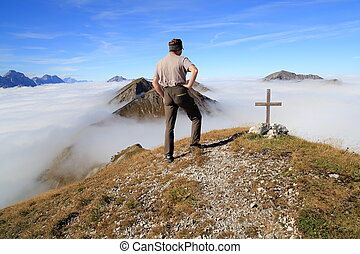 hiker is standing on the top of a mountain
