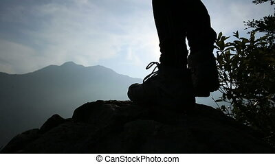 hiker legs on mountain peak rock
