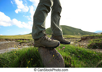 hiker legs stand on rock outdoors