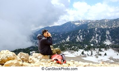 Hiker looking at binoculars at amazing view near the 2365m...