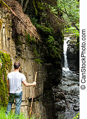 Hiker Looking at the Waterfall in the Wild Nature on a Rainy...