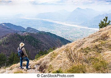 Hiker looking from Monte Chiampon to Friuli-Venezia Giulia -...