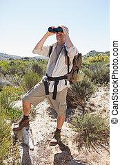 Hiker looking through binoculars on country trail