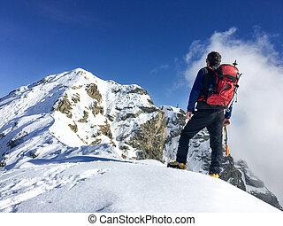 Hiker looks at a winter mountain landscape. European Alps.