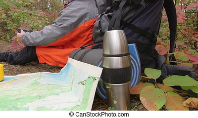 Hiker looks at map on tablet computer in the woods