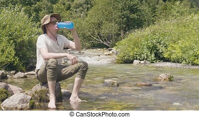 Hiker man drinking spring water from bottle on river shore in mountain forest