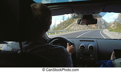 Hiker man driving a car in the long road through beautiful countryside along mountains