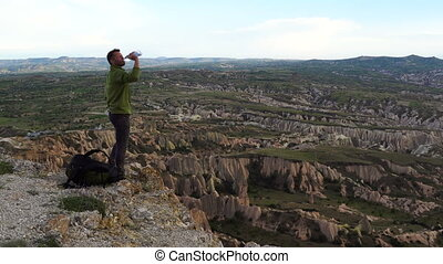 Hiker Man Drop his Backpack and Drink Water on the Top of Mountain in Cappadocia, Turkey.