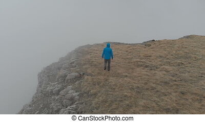 Hiker man in a blue jacket with backpack is walking and...