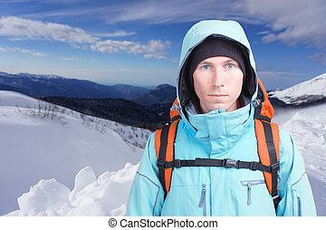 Hiker man in winter mountains.