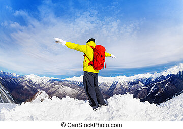 Hiker man on top of snow mountain peak