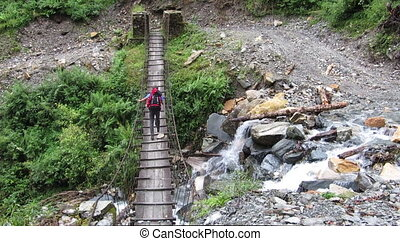 Hiker man passing on a suspension bridge in the Himalayas