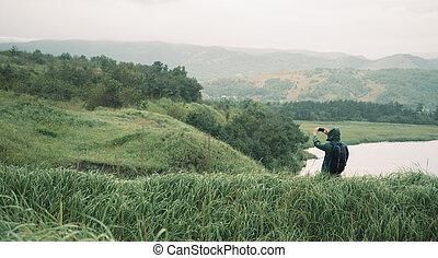 Hiker man photographs the summer landscape