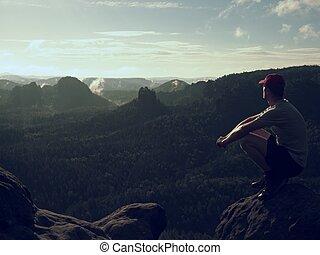 Hiker man take a rest on mountain peak. Man sit on summit,