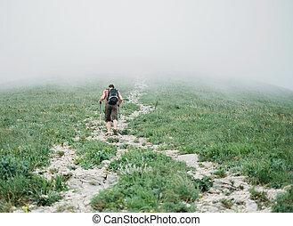 Hiker man walking in the mist