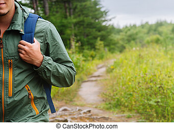 Hiker man walking on path in summer - Smiling young hiker...