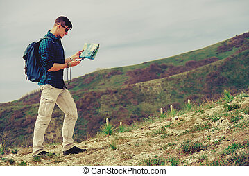 Hiker man with equipment walking in the mountains