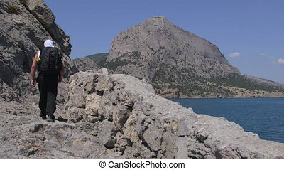 Hiker on a cliff near the sea