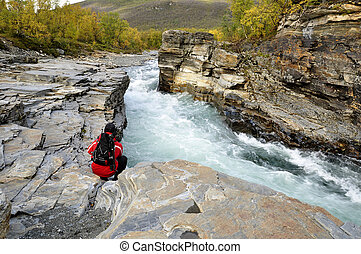 Hiker on mountain landscape in north of Sweden