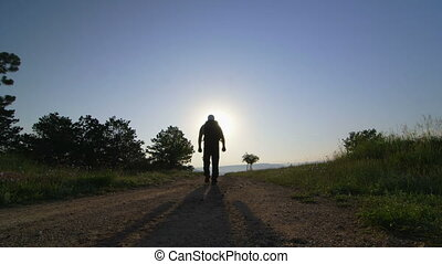 Hiker on the trail at sunrise - Hiker on the trail at...